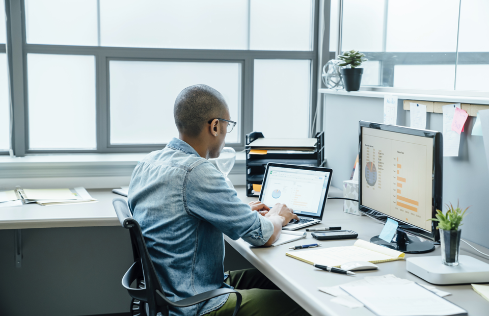 Homme assis à un poste de travail face à des ordinateurs mettant en avant des données.