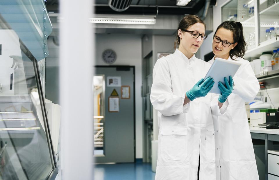 Deux femmes scientifiques dans un laboratoire, discutant de données médicales.