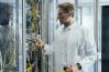 Un homme branche une fibre dans une armoire informatique