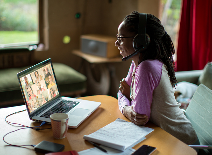 A woman attends an online course from her living room.