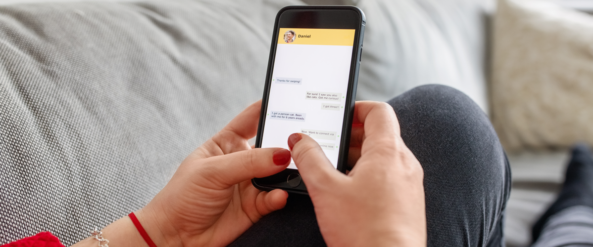 A person on her couch looks at the conversation with a chatbot on her phone.