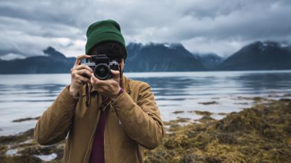 Un homme au bord de l'eau prend une photographie